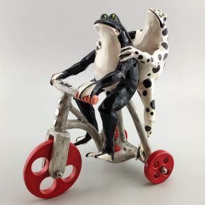 whimsical clay sculpture frogs riding tricycle